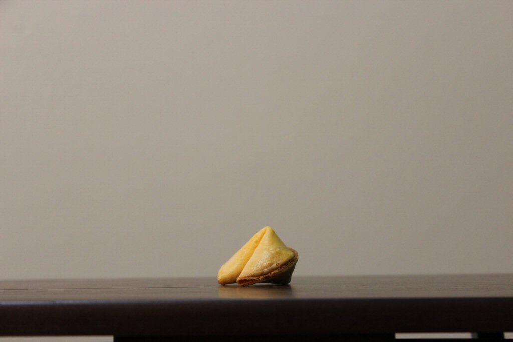 Lonely Unopened Fortune Cookie Sitting on a Table Waiting to be Eaten